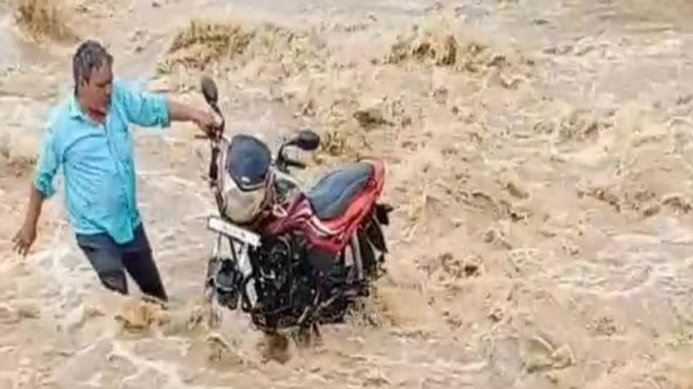 નદીના ધસમસતા પ્રવાહમાં બાઇક ચાલક ફસાયો, જીવના જોખમે બાઇક તણાવતું બચાવા અનેક પ્રયાસો કર્યા